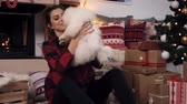 Woman cuddling her cute little dog at christmas