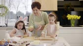 rodar : Grandmother teaching children how to bake cookie Stock Footage