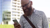 kel : Cheerful businessman texting outdoors Stok Video