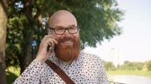 careca : Hipster man talking by mobile phone outdoors Stock Footage