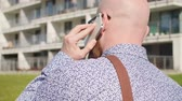 kel : Rear view of man talking by mobile phone outdoors Stok Video