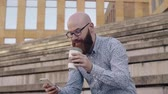careca : Man drinking coffee and using mobile phone outdoors