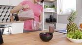 část : Part of woman pouring a jar of smoothie at kitchen