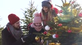 süsleme : Parents with child decorating a christmas tree at forest