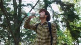 sedento : Backpacker drinking water in the forest Vídeos