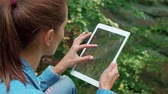 right : Woman using a tablet during hiking trip