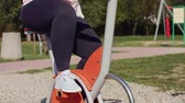 copiadora : Tired woman using exercise bike in public park Stock Footage