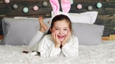 Smiling girl with bunny ears lying on the bed Archivo de Video