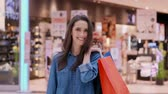 paper bag : Waist up of turning woman with shopping bags Stock Footage