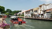 колониальный : Malacca, Malaysia - May 5, 2019:  Riverside scenery of a cruise full of passengers crossing by the Malacca River. It has been listed as UNESCO World Heritage Site since 772008. Стоковые видеозаписи