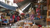 Maeklong,Thailand - Nov 7 ,2019 : Tourists can seen exploring and shopping along the Maeklong Railway Market.It is a Thai market selling fresh vegetables,food, fruit,as well as souvenirs and clothing.