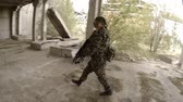 perseguição : Soldiers with weapons goes on an abandoned factory Stock Footage