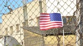 American flag on closed factory gates 4K