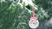 White Christmas bauble hanging on snowy fir tree 4K