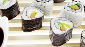 унаги : Roll with Cucumber   Cream Cheese with raw Tuna and Salmon inside. on wooden grid . Isolated over white background . Japanese traditional Cuisine
