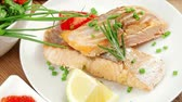 salmon pink : healthy sea food : roasted pink salmon fillet with vegetable salad   chives  lemon  red caviar in white bowl  with pepper in grinder and cutlery on white dish over wooden table