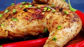 entrees : roast meat : chicken legs garnished with green onion pens and peppers on wooden plate over blue wooden background