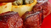 preparations : european food: roast beef meat over red plate isolated on white background with hot peppers  capers   olives oil   and bbq sauce