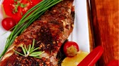 seabass : served main course on wood: whole fried seabass on plate with lemons tomatoes and peppers Stock Footage
