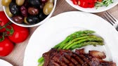 chřest : meat table : rare medium roast beef fillet and pasta with tomatoes asparagus and several kinds of olives  served on white dish over light wood Dostupné videozáznamy