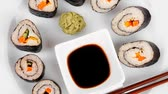 soja : Maki Sushi : Maki Rolls and California rolls made of fresh raw Salmon(sake)  Tuna(maguro) and Eel(unagi) . on white dish with sticks isolated over white background Vídeos