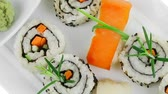 унаги : Maki Rolls and California rolls made of fresh raw Salmon  Tuna and Eel with Cream Cheese and Avocado . Isolated over white background . on long white plate . Maki Sushi and Nigiri