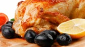 single roast : baked meat : fresh whole chicken with black olives and raw tomatoes on wooden board isolated over white background Stock Footage