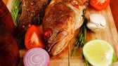 seabass : main portion of two grilled fish served on wooden table with castors Stock Footage