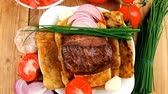 charbroiled : roast meat : beef ( lamb ) steak garnished with onion   tomatoes salad and chives  on wooden table