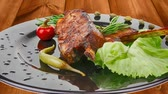 entrees : savory plate: grilled ribs over black with peppers and green salad Stock Footage