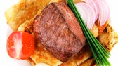 charbroiled : roast meat : beef ( lamb ) steak garnished with onion   tomatoes salad and chives isolated over white background