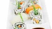унаги : California Roll with Avocado and Salmon  Cream Cheese and Raw Salmon inside. on long white plate . isolated over white background . Maki Sushi and Sashimi Стоковые видеозаписи
