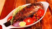 seabass : main course: whole fryed sunfish on wooden table with lemons and peppers Stock Footage