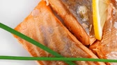 entrees : savory fish portion : grilled norwegian salmon fillet with green chinese onion  and lemon slice on white plate isolated over white background Stock Footage