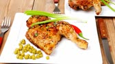 roast ham : roast chicken : legs garnished with green peas   peppers   and cutlery on white plates over wooden table