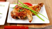 roast ham : meat : chicken quarters garnished with green sweet peas and and cutlery on white plates over wooden table Stock Footage
