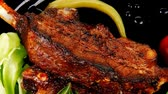 capers : image of served meat: spiced barbecued ribs on black plate with peppers chives and capers