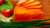 гауда : orange aged delicious cheddar cheese chop with slice on wooden plate with tomatoes   chives and salad . 1920x1080 intro motion slow hidef hd