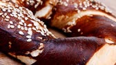 topped : fresh mixed pretzels topped by sesame on wooden table 1920x1080 intro motion slow hidef hd Stock Footage