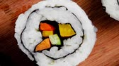 сакэ : Japanese Cuisine - Maki Roll with Deep Fried Vegetables inside . on wooden plate . 1920x1080 intro motion slow hidef hd