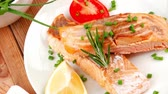 salmon pink : savory fish portion : roasted norwegian salmon chunks with lemon and vegetable salad   rosemary twig and red caviar in white bowl over wooden table 1920x1080 intro motion slow hidef hd Stock Footage