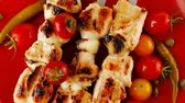capers : fresh grilled chicken shish kebab served wtih tomato cherry hot peppers on skewers over red plate 1920x1080 intro motion slow hidef hd
