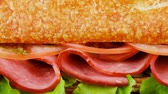 salami slice : sandwich with smoked sausage on wooden plate over black background 1920x1080 intro motion slow hidef hd