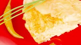 cheese piece : food : cheese casserole piece on red plate served with garlic   chives and tomatoes 1080p 1920x1080 intro motion slow hidef hd Stock Footage