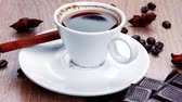 food and drink : sweet hot drink : black Turkish coffee in small white mug with coffee beans spilled over a wooden table with stripes of dark chocolate and cinnamon stick 1920x1080 intro motion slow hidef hd
