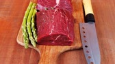 flank : red fresh raw beef veal fillet with asparagus and stainless steel chef knife on cutting plate over wooden table prepared to use 1920x1080 intro motion slow hidef hd Stock Footage