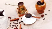 food and drink : sweet hot drink : black turkish coffee in small white mug with mortar and pestle   coffee beans in white bag   copper old style cezve full hot coffee  decorated with cinnamon sticks and anise stars 1920x1080 intro motion slow hidef hd