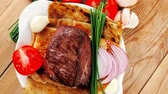 charbroiled : roast meat : beef ( lamb ) steak garnished with onion   tomatoes salad and chives  on wooden table 1920x1080 intro motion slow hidef hd Stock Footage
