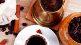 food and drink : sweet hot drink : black arabic coffee in small white cup with mortar and pestle   bag full beans  copper old style cezve   decorated with cinnamon sticks and anise stars 1920x1080 intro motion slow hidef hd