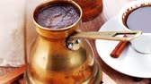 cinnamon sticks : sweet hot drink : black arabic coffee in small white cup with mortar and pestle   bag full beans  copper old style cezve   decorated with cinnamon sticks and anise stars 1920x1080 intro motion slow hidef hd